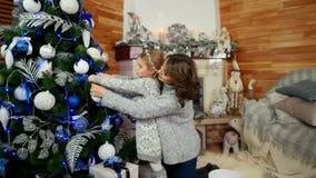 Familjen som dekorerar en julgran, modern och dottern förbereder sig för ferien för det nya året, lycklig familj hemma in lager videofilmer