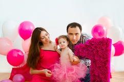 Familjen som firar den första födelsedagen av, behandla som ett barn dottern Arkivfoto