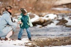 familjen som har floden, går vinter royaltyfri foto