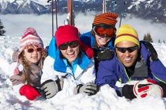 Familjen som har gyckel skidar på, ferie i berg Royaltyfria Bilder