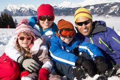 Familjen som har gyckel skidar på, ferie i berg Fotografering för Bildbyråer