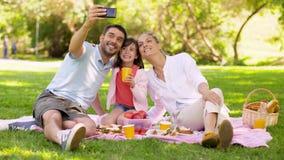 Familjen som har picknicken och tar selfie på, parkerar arkivfilmer
