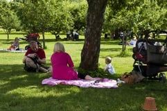Familjen som kopplar av på gräs i stad, parkerar Royaltyfri Fotografi