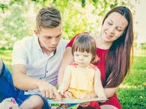 Familjen som läser en bok på, parkerar royaltyfria bilder
