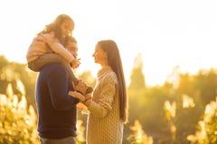 Familjen som spelar i höst, parkerar att ha gyckel på solnedgången Arkivfoton
