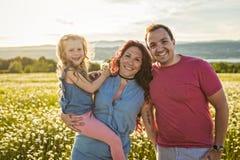 Familjen som spenderar utomhus tid avlar tillsammans, modern, och dottern har gyckel under solnedgången royaltyfri bild