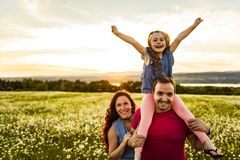 Familjen som spenderar utomhus tid avlar tillsammans, modern, och dottern har gyckel under solnedgången royaltyfri foto