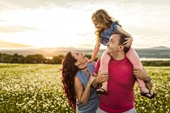 Familjen som spenderar utomhus tid avlar tillsammans, modern, och dottern har gyckel under solnedgången arkivfoton