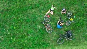 Familjen som utomhus cyklar på flyg- sikt för cyklar från över, aktiva föräldrar med barnet, har gyckel och kopplar av på gräs, f arkivbild