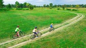 Familjen som utomhus cyklar på flyg- sikt för cyklar från över, den lyckliga aktiva modern med barn, har gyckel royaltyfri fotografi