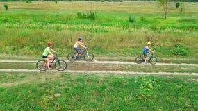 Familjen som utomhus cyklar på flyg- sikt för cyklar från över, den lyckliga aktiva modern med barn, har gyckel, familjsport Royaltyfria Bilder
