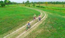 Familjen som utomhus cyklar på flyg- sikt för cyklar från över, den lyckliga aktiva modern med barn, har gyckel, familjsport Arkivfoto