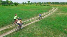 Familjen som utomhus cyklar på flyg- sikt för cyklar från över, den lyckliga aktiva modern med barn, har gyckel, familjsport Royaltyfria Foton