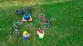 Familjen som utomhus cyklar på flyg- sikt för cyklar från över, lyckliga aktiva föräldrar med barnet, har gyckel och kopplar av,  Royaltyfri Fotografi