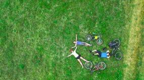 Familjen som utomhus cyklar på flyg- sikt för cyklar från över, lyckliga aktiva föräldrar med barnet, har gyckel och kopplar av p royaltyfria foton