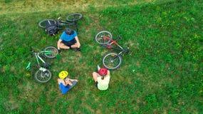 Familjen som utomhus cyklar på flyg- sikt för cyklar från över, lyckliga aktiva föräldrar med barnet, har gyckel och kopplar av p royaltyfri fotografi