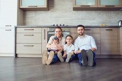 Familjen spelar gyckel på golvet inomhus arkivfoton