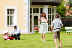 Familjen spelar i sommar framme av deras hus royaltyfri fotografi