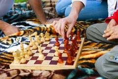 Familjen spelar schack utomhus royaltyfri fotografi