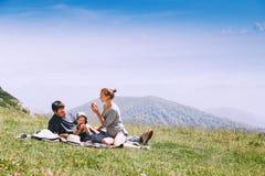 Familjen spenderar tid på naturen i bergen royaltyfri bild