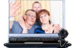Familjen talar på videokommunikationerna Royaltyfri Bild
