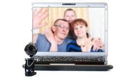 Familjen talar på videokommunikationerna Royaltyfria Bilder