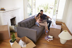 Familjen tar ett avbrott på den Sofa Using Laptop On Moving dagen Royaltyfri Bild