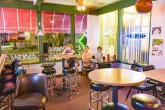 Familjen tycker om den typiska pizzarestaurangen och stången i sjön Havas Arkivfoto