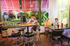 Familjen tycker om den typiska pizzarestaurangen och stången i sjön Havas Royaltyfri Foto