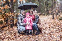 Familjen under paraplyet i höststad parkerar, den lyckliga familjen arkivbild