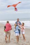Familjen uppfostrar flickabarn som flyger draken på stranden Arkivbild