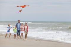 Familjen uppfostrar flickabarn som flyger draken på stranden Arkivfoton