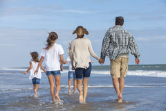 Familjen uppfostrar flickabarn som går på stranden Arkivbilder
