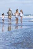 Familjen uppfostrar flickabarn som går på stranden Arkivfoto