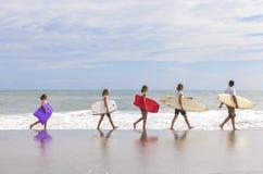 Familjen uppfostrar flickabarnsurfingbrädor på stranden Royaltyfri Bild