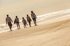 Familjen uppfostrar flickabarnsurfingbrädor på stranden Royaltyfria Bilder