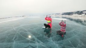 Familjen utbildar övningsyoga i vinter Kvinnan är gör sträckning och meditation på is i natur Fostra och dottern stock video