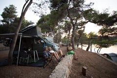 Familjen vilar i skog bredvid den campa skåpbilen royaltyfri foto