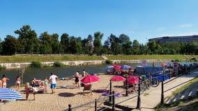 Familjer med barn som solbadar på flodbankerna Arkivbild