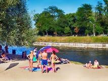 Familjer med barn som solbadar på flodbankerna Royaltyfria Bilder