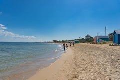 Familjer med barn som in tycker om sommardag på den Brighton stranden arkivbilder