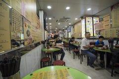 Familjer tycker om deras matställear på en restaurang i Kowloon, Hong Kong fotografering för bildbyråer