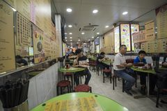 Familjer tycker om deras matställear på en restaurang i Kowloon, Hong Kong royaltyfri foto