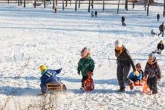 Familjer tycker om sledding på en snöig kulle Fotografering för Bildbyråer