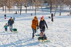 Familjer tycker om sledding på en snöig kulle Arkivfoton