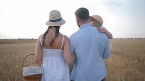 Familjförhållande, ung lantlig familj som går och talar med korgen av nytt bakade bröd och bullar i veteskörd stock video