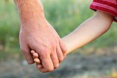 Familjfadern och barnsonen räcker den utomhus- naturen Royaltyfri Bild