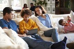 Familjfamilj för tre utveckling som hemma spenderar tid i deras vardagsrum, föräldrar och unga ungar i förgrunden, morföräldrar arkivbilder