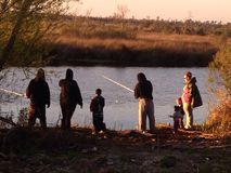 Familjfiske på flodstranden på flodarmen Royaltyfri Fotografi