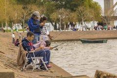 Familjfiske på kusten av floden i Montevideo Arkivfoto